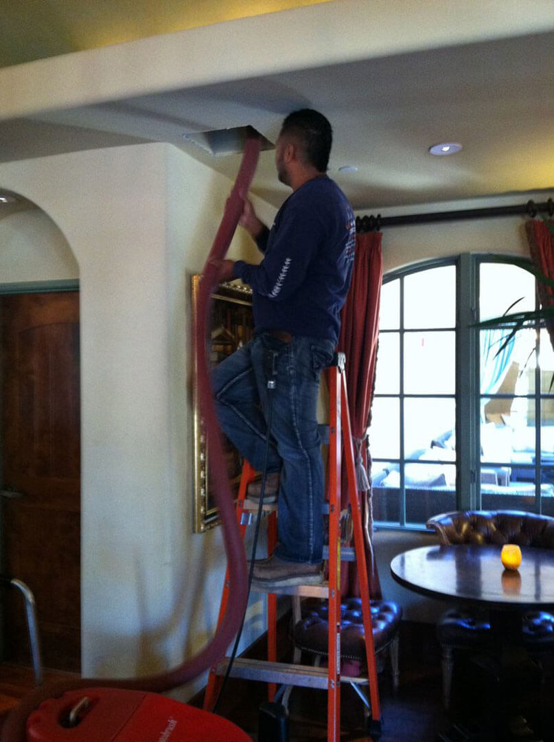 HVAC technician in Morgan Hill cleaning air ducts