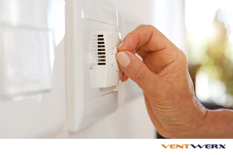 Hand adjusting a thermostat on wal air conditioning